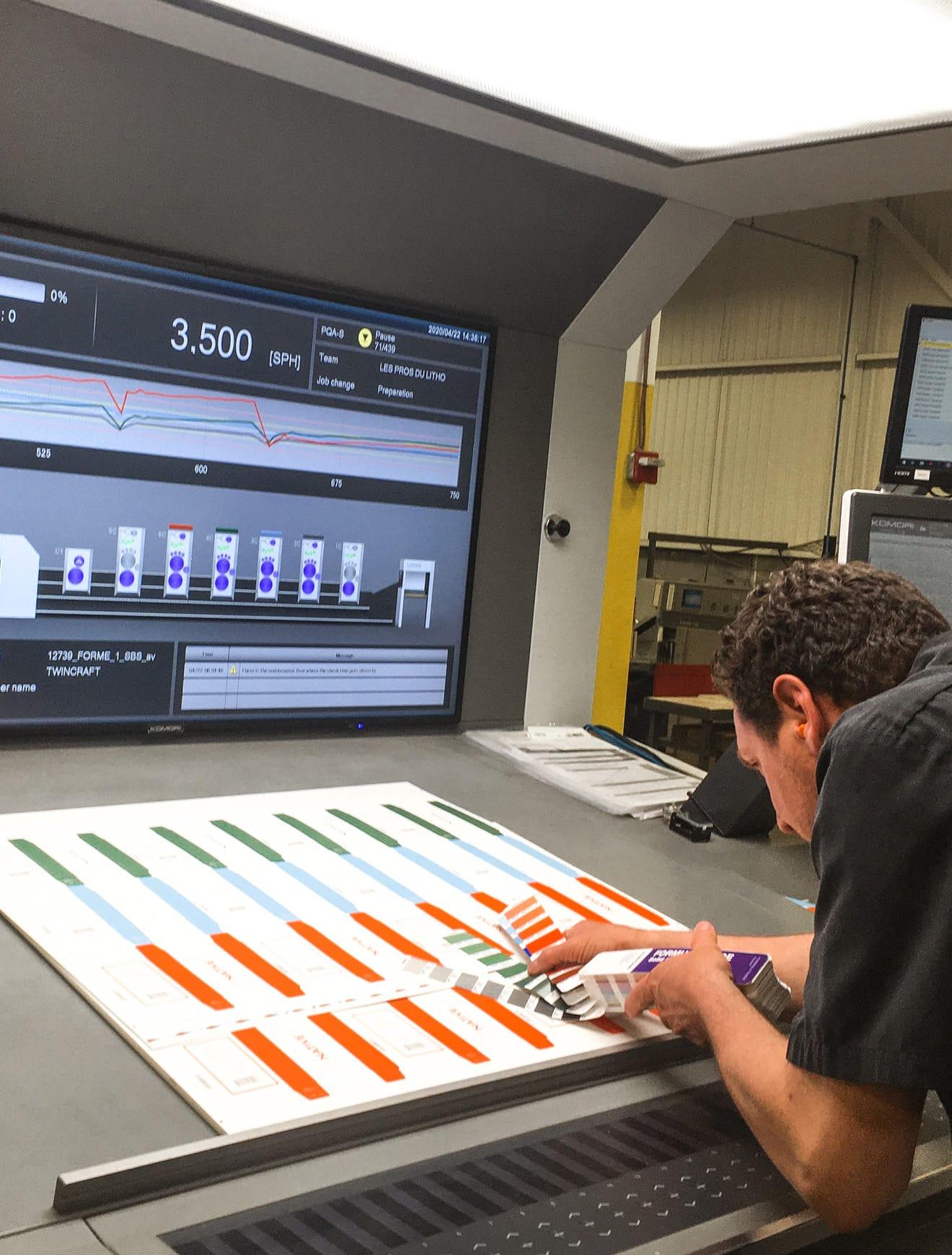 Employé qui fait une inspection en ligne sur la presse lithographie