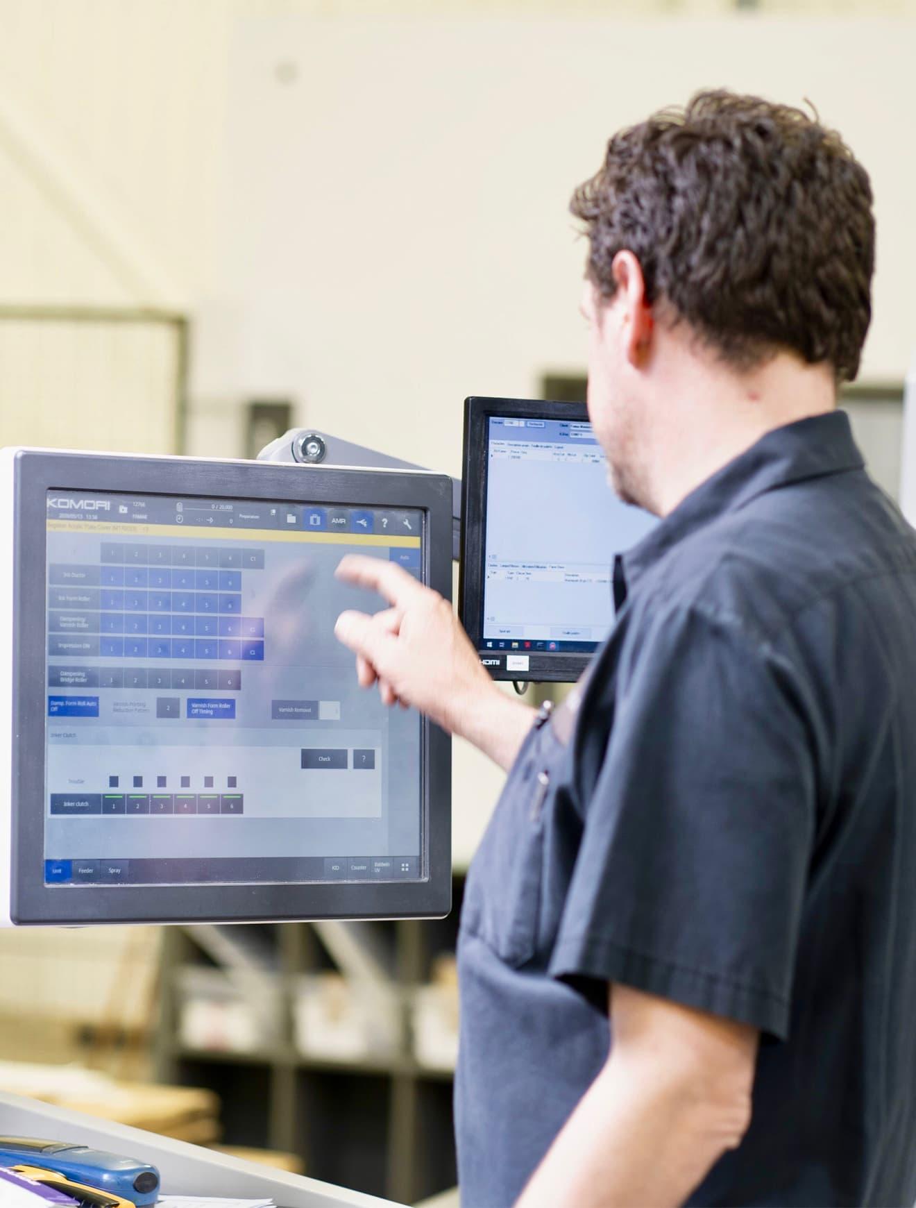 Employé qui regarde l'inspection sur la presse lithographie