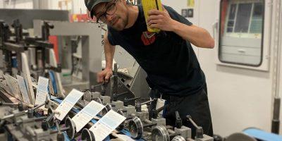 Employé qui regarde la production de boîtes sur la colleuse