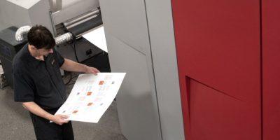 Employé qui inspecte une feuille de la presse numérique